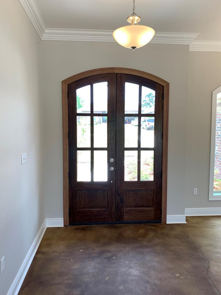 Inside entry with double wood curved doors.