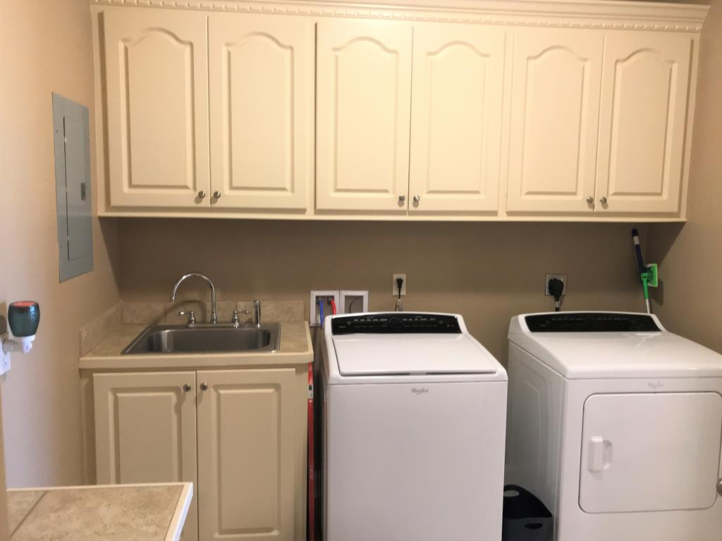 Utility room has cabinetry, sink, folding table.